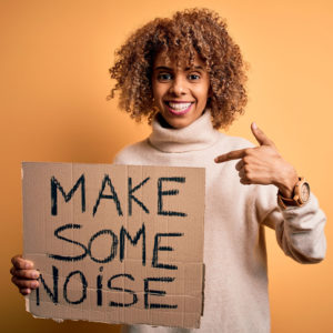 African american activist woman asking for revolution holding banner with make noise message with surprise face pointing finger to himself